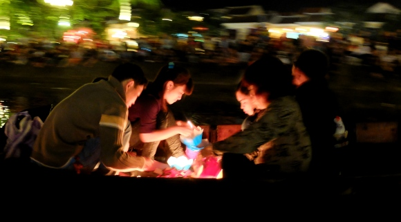 A family lighting candle-boxes that float down the Thu Bon River